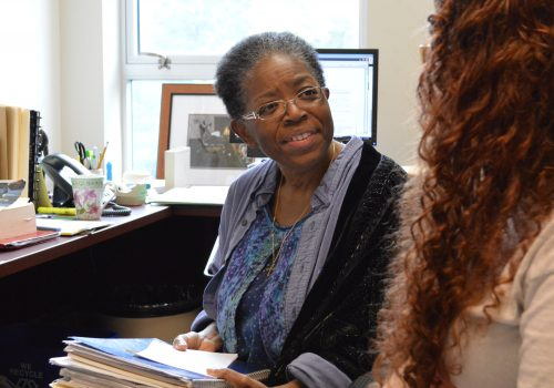 Dee James sitting with a student in her office