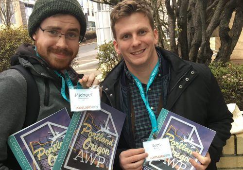 Two students posing in front of the Portland convention center, holding AWP conference materials.