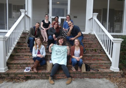 Eight Sigma Tau Delta students and Dr. Boyle seated on the front steps of Flannery O'Connor's house in Milledgeville, Georgia.
